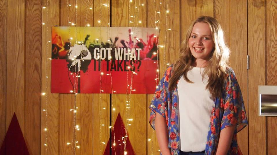 Lily Moram looking excited as she poses with the CBBC Got What It Takes logo